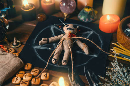 Voodoo doll studded with needles with pierced red rag heart on pentagram and around burning candles. Spooky or eerie magical esoteric ritual.
