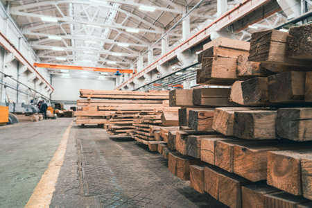 Woodwork factory with stacks of wood and equipment machinery. Professional industrial carpentry manufacturing.