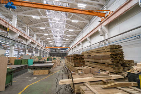 Inside huge factory workshop interior with stacks of wood for making molds. Woodwork manufacture production industry.