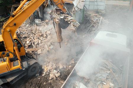 Excavator bucket loads industrial debris into truck. Process of demolishing and destruction old house. Release of quarters for new development. Foto de archivo