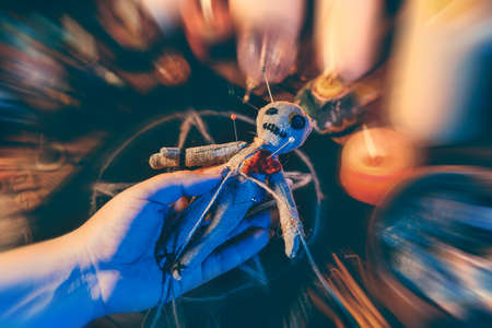 Female hand holds voodoo doll on blurred background. Ancient dark evil witchcraft of punishment and revenge.