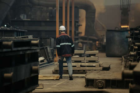 Worker in metallurgical plant foundry. Heavy industry.