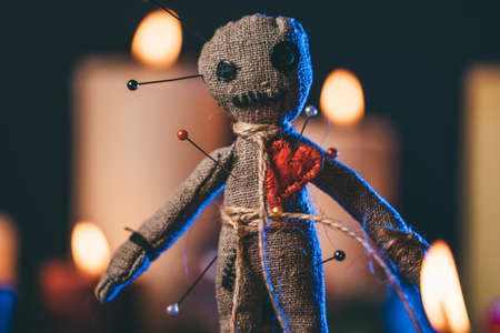 Voodoo Magic concept. Witchcraft with Voodoo doll. Close-up of rag puppet nipped with needles.