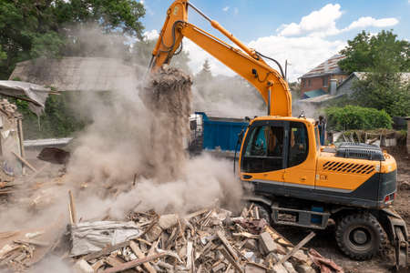 Demolition of building by industrial excavator. Bucket breaks walls and roof of old house full of dust.