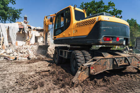 House demolition process. Big yellow excavator breaks building for new construction Foto de archivo