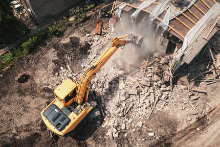 Demolition of old house building process for new construction by excavator bucket, aerial view. City development