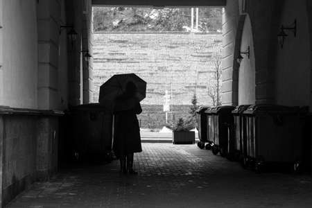 A woman under an umbrella in a dark arch next to garbage cans