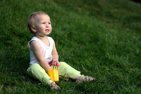 Little boy with pail sits on a green grass  Stock Photo