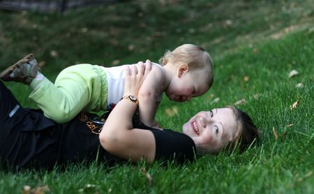 Mother with her son play on a green grass