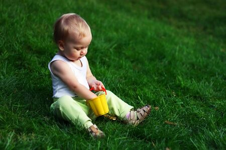 Little boy with pail sits on a green grass