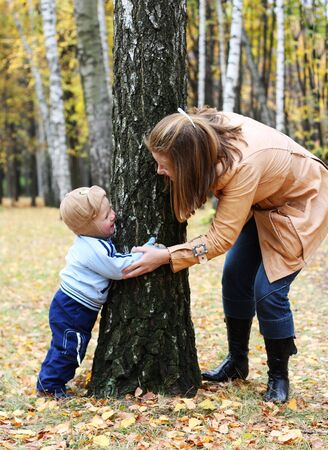 Mother with son play seek and hide in a park