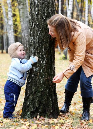 Mother and son play hide-and-seek in a park Stock Photo