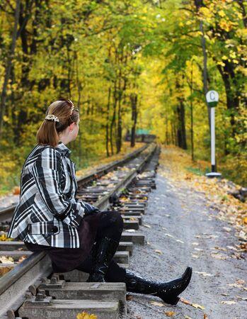 Le giovani donne si siede su una rotaia na bosco in autunno Archivio Fotografico