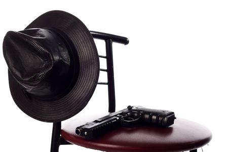 Pistola e il cappello sulla sedia isolata sul bianco