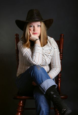 Cowgirl in a jeans sitting on a chair  photo