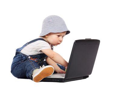 Piccolo ragazzo seduto con un computer portatile isolato sul bianco  Archivio Fotografico