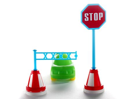 Car behind barrier with stop road sign on white background