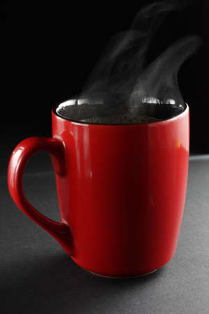 Red cup of coffe on a dark background