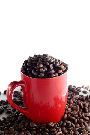 Tazza rossa piena di chicchi di caff� torrefatti marroni