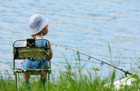 chlapec: Little boy with fishng rod sitting near the lake