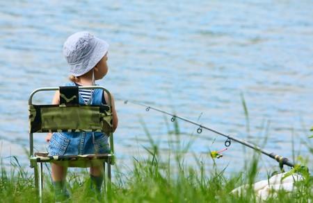 Ragazzino con asta fishng seduto vicino al lago