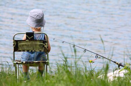 Little boy con asta fishng seduto vicino al lago