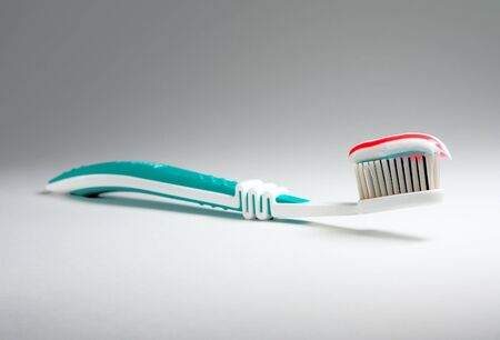 Colored toothpaste at a toothbrush at light background