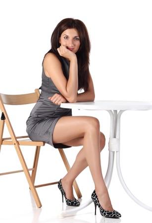 Ragazza seduta su una sedia vicino alla tabella
