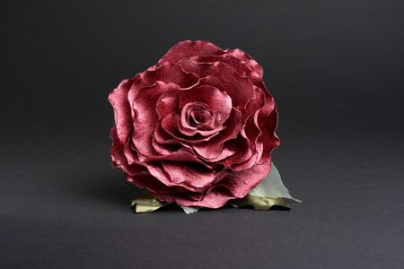 Artificial red rose at dark background