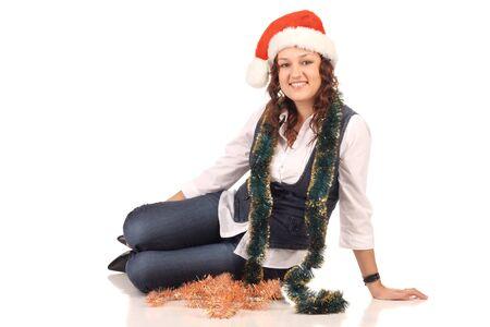 Ragazza in un cappello di Babbo Natale con decorazioni di Natale isolato in bianco