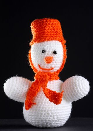 White snowman made from threads at the dark background photo