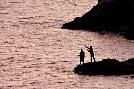 Two men fishing from the shore photo