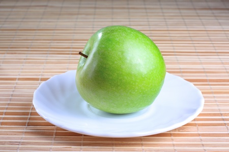 Green apple on the saucer at the wooden texture background