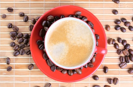 Cup of coffee with roasted beans at wooden background photo