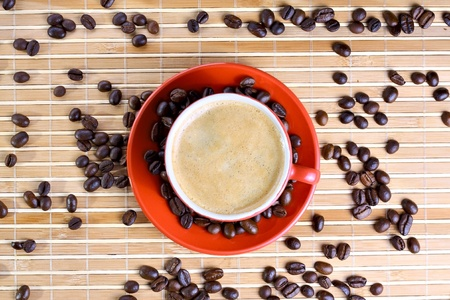 Cup of coffee with roasted beans at wooden background Stock Photo