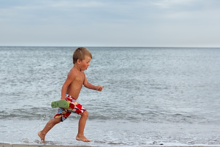 Little boy running at the shore near the sea photo