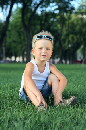 Little boy sitting in the park on a grass