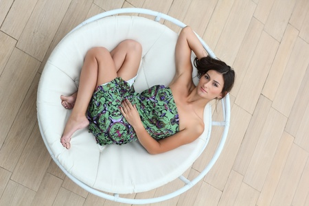 Young woman lies in the circle deck chair Stock Photo