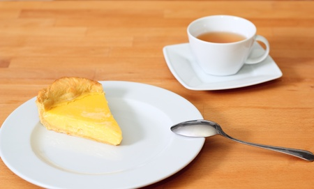 Torta al limone e t� sul piattino a tavola Archivio Fotografico