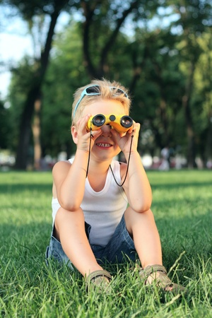 Little boy looking through the binoculars in th park Stock Photo - 16937096