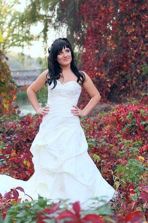 Ragazza in un vestito diserbo in un parco tra le foglie verdi e rosse