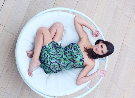 Young woman lies in the circle deck chair photo