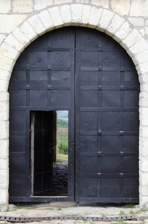 view of a wooden doorway: Big iron gates with opened door in the castle