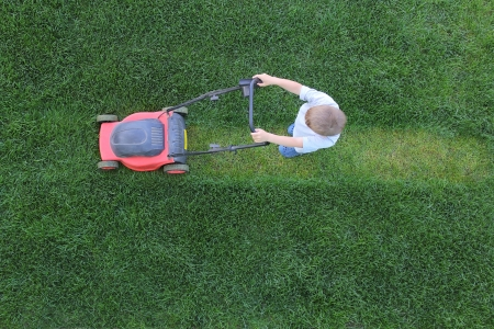 Little boy cuts a lawn using lawn-mower Stock Photo
