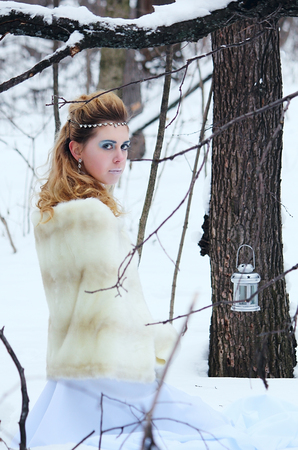 Portrait of beautiful girl in the winter forest among white snow