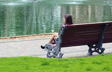Woman sitting near the river at the bench