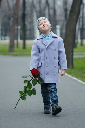 Little romantic boy with rose walking in the park