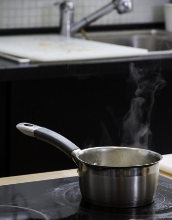 Little saucepan with boiling water on the plate