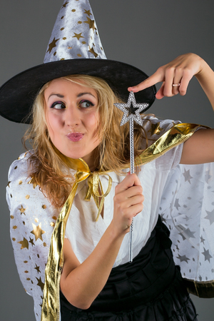 Young witch with magic wand at grey background Stock Photo