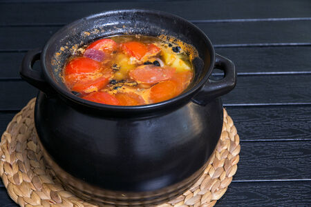 Soup in the black saucepan at wooden table